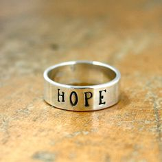 "Custom stamped wide sterling silver ring. This ring is stamped ""HOPE"" but you can customize it with a name or other inspirational word. $59"