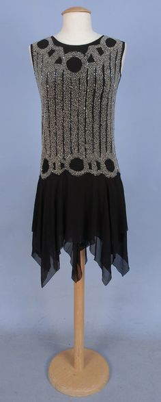 BEADED CHIFFON DRESS, 1920's. Black silk decorated with vertical bands of crystal beads with rings along neckline and low waist, double skirt with alternating handkerchief points.