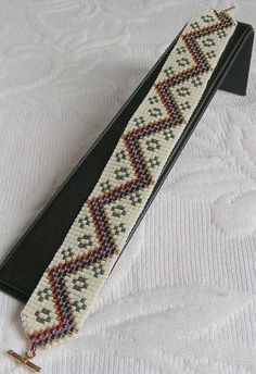 """A narrow bracelet with lots of personality. The metallic colors on a cream background stand out to catch the eye. Easy to wear on many occasions. It is made on a loom with thousands of Japanese Delica beads which are of the highest grade and quality. The piece is 3\/4"""" wide by 7"""