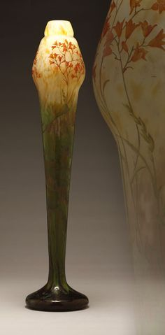 A tall Daum Nancy Lily cameo art glass vase, Early 20th century, signed in relief ''Daum / Nancy'' with Croix de Lorraine, with stepped gourd-form top decorated with small orange lily sprays over a tapering attenuated body decorated with yellow-green foliage, above a circular mottled aubergine foot.