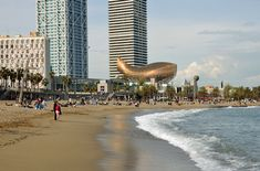 """Barceloneta Beach, Barcelona, with Frank Gehry's abstract fish sculpture """"Peix D'Or.""""  (photo by Phillip Lange for Shutterstock)"""