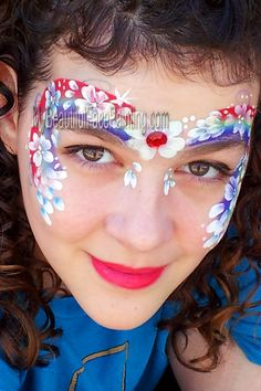 Ultimate rainbow and flowers face paint. Rainbow is Tag regular rainbow. Flowers and Dots-DFX white with touches of blue and purple. Red stone attached with eyelash glue.