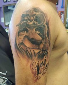 Black tattoo with head of Mufasa and little simba on half-sleeve