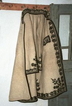Romanian costume Vâlcea Long felted overcoat called a Şuba made of white woven woollen cloth, and decorated with black braid on front edges, collar, sleeve edges and pocket flaps.    Photo taken at Bujoreni Open Air Museum, Râmnicu Vâlcea in July 1999.