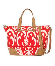 "Stella & Dot Getaway in Red Ikat- This fun printed tote is a traveler's secret weapon: Not only does it boast a detachable shoulder strap and spill-resistant lining, it also ""grows"" when you need more space for souvenirs. Just unzip the center zipper to expand the main compartment by an extra 4.25 inches."