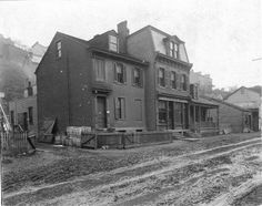 L.F. Schodde Meat market at 529 East Street in Allegheny City, Allegheny County, PA looking northwest in 1899. Anna Street is located behind brick buildings. View of muddy East Street prior to improvement. Current location of I-279 on Pittsburgh's North Side. Date ca. 1899-1905