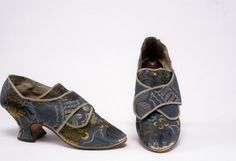 """Ladies Shoes, New England, Gray, Winthrop (Maker), 1765-1775. Upper of dark gray silk brocaded w/ large stylized flowers w/ gold & silver metallic thread & geometric patterned ground; thick 2"""" heel; oval toe; straight side seam; square tongue. Brocade,  Fiddle Thread, Hand Stitched, Silk brocade (textile), metallic (color attribute), silk stitching thread. Historic New England."""