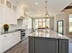 White kitchen cabinetry with grey accent island. Chrome hardware accents with quartz and granite countertops.