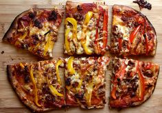 rectangular thin pizza topped with cheese, red and yellow sliced sweet peppers and spicy sausage crumbles