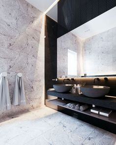 Black double ceramic sink bowls on black plinth with warm white natural stone floor & walls