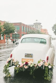 """Brides.com: . A gorgeous garland of lush greenery, pink-and-burgundy dahlias, and blush roses, plus a """"We Did"""" frame, instantly upgrade this ride."""