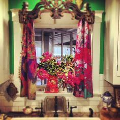 Amazing look for this kitchen window. Colorful drapes under a wooden valance. This looks like it would come to you in a dream if you were a genius. Fantastic combination !