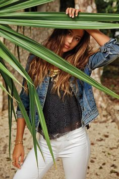 Model wears denim jacket, lace top and white jeans from American Eagle