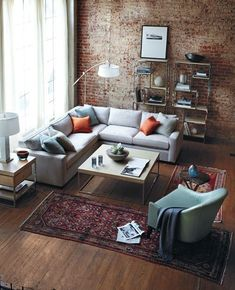 grey couch with pops of orange and soft teal / brick wall / high ceilings