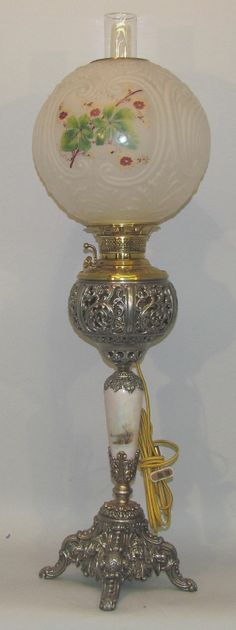 A Victorin banquet table oil lamp, ornate cast white metal base with decirated stem having open work scrolled rexervoir and a decorated frosted globe shade. America, circa 1885-1895