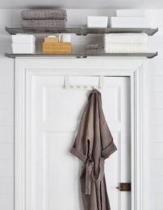 Металлические полки над дверью предназначены для хранения полотенец и других вещей про запас, а банные халаты можно повесить на дверные крючки.