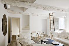 Blanc avec un parquet magnifique au large latte et l'originalité de la décoration au mur. Causeuses avec de gros coussins-oreillers blancs.