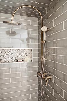 Gray walk in shower boasts ceiling and walls clad in gray tiles fitted with a white and gray mosaic tiled shower niche as well as a vintage style exposed plumbing shower kit