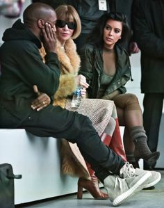 Kanye West, from left, Vogue editor Anna Wintour, and Kim Kardashian chat before the showing West's Yeezy Boost shoe line for Adidas on Thursday, Feb. 12, 2015, during Fashion Week in New York. (AP Photo/Bebeto Matthews)