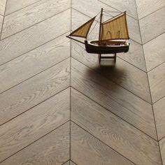 Chevron wood floor this plus white walls and pendants for Chevron laminate flooring