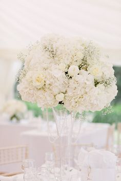 Tall flute vases of hydrangea, gypsophila and peonies at Ardington House, Oxfordshire, Joanna Carter wedding flowers