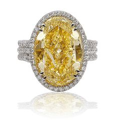 FANCY COLOURED YELLOW OVAL DIAMOND RING WITH WHITE DIAMOND HALO. 8.72 CARATS. LOUIS NEWMAN & COMPANY