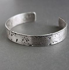 Extra thick gauge sterling silver has been hand forged into this rugged, rustic men's cuff bracelet. The heavy hammered texture and oxidized finish reminds me of concrete. Each bracelet is unique and made individually; no two bracelets will be the same! Silver band measures .5 inch (1.3 cm)