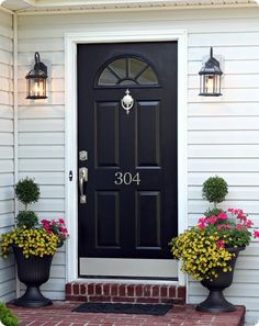 Curb appeal: black front door, new numbers, urns of flowers, up to date lighting, welcome mat