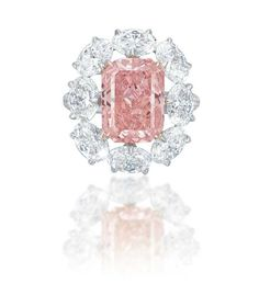 A MAGNIFICENT COLOURED DIAMOND RING. Set with a fancy vivid pink rectangular-cut diamond, weighing approximately 5.18 carats, within an oval-shaped diamond surround, mounted in gold, ring size 6. Accompanied by report no. 2165887854 dated 7 January 2015 from the GIA Gemological Institute of America stating that the 5.18 carat diamond is Fancy Vivid Pink colour, VS2 clarity