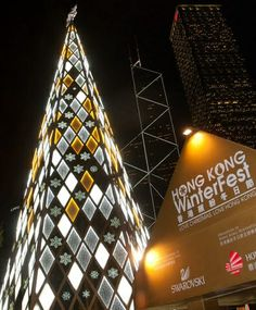 Across the water in another Chinese special administrative region, the tallest Christmas tree in Hong Kong glows with its Swarovski crystal bands. The Bank of China building lights up the background.