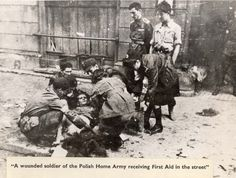Warsaw, Poland, A wounded soldier from the Polish Home Army receiving first-aid in the street.
