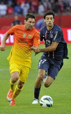 El delantero argentino del FC Barcelona Lionel Messi pelea por el balón con su compatriota Javier Pastore