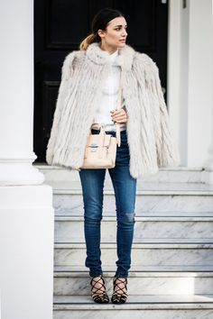 Anisa Sojka wearing a white vintage fox fur jacket, white Wåven shirt and blue denim jeans, beige 3.1 Phillip Lim mini pashli and black, red and orange strappy sandal heels. Fashion blogger street style shot in London by Cristiana Malcica.
