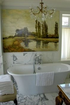 So pretty. Marble floor and wainscot, large painting over tub, chandelier, freestanding tub.
