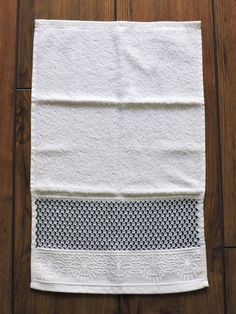 Pode ser usada como toalha de mão ou de rosto  Bordado em PONTO CRIVO, feito a mão pela artesã Cristina Panontin  Bordado em linha preta, cinza e branca  Toalha branca ótima qualidade  Tipo de tecido: 97% algodão + 3% viscose  Dimensão da toalha: 33 x 50cm  Marcas de dobras indicam a goma do teci...