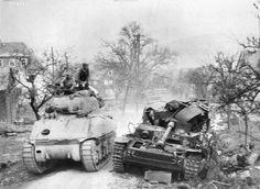 Un Medium Tank M4A1 dont l'avant a été renforcé dépasse la carcasse d'un Panzer IV. Nous sommes sur le front de l'Ouest, peut-être en 1945.
