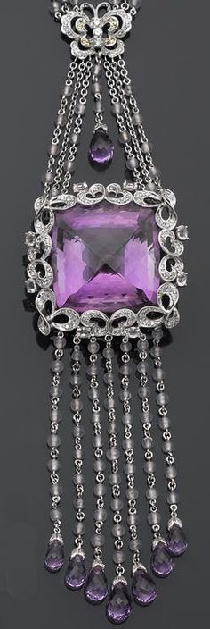 An amethyst, diamond, and gem-set necklace  featuring a square briolette-shaped amethyst, within an openwork frame, suspended from a triple-link chain of butterfly motif, completed by fringe, set throughout with round brilliant-cut diamonds, bead and oval-shaped rose quartz, circular-cut yellow sapphires, and briolette-shaped amethysts; estimated total diamond weight: 1.75 carats; mounted in eighteen karat white gold; length: 25½in.