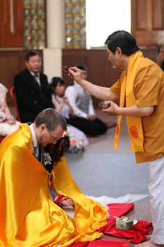water blessing Buddhist wedding tradition...Orange robe over the tux during ceremony