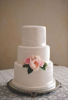 Patti Cakes created this three-tiered white cake adorned with a cluster of pink garden roses