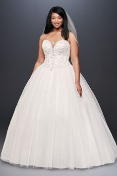If a bit of sparkle on this plunging, illusion-inset plus-size wedding gown catches your eye, look closely: the gleam comes not only from the beautifully hand-beaded bodice but also from a sequined la
