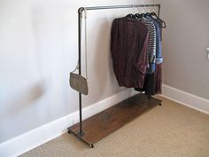 Use metal piping to put together a cheap & easy garment rack.