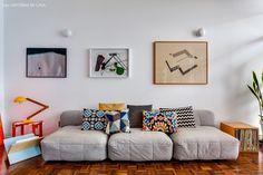 sofá cinza aconchegante com muitas almofadas estampadas e quadros na parede de fundo