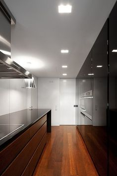 Making the narrowest kitchen perfect. Black and wood.