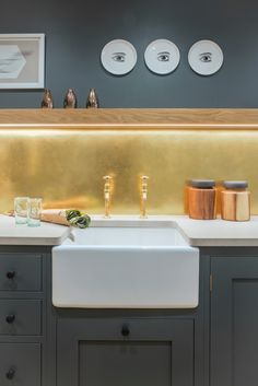 This shaker style kitchen is painted with Farrow & Ball Down Pipe on both the cabinetry and the walls. This creates a feature of the brushed brass splashback. The floating oak shelf with LED lights and Concreto Biscotte worktop add a contemporary flare while the Classic Belfast under mounted sink and Perrin & Rowe Mayan tap mix in a bit of tradition.