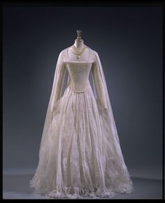 """Evening dress, Vivienne Westwood, 1994, British, flocked tulle and satin. """"Vivienne Westwood created this romantic dress for Lady Bianca Job-Tyoran to wear to Queen Charlotte's Ball in 1994. This élite charity event has effectively taken over the role of court presentations: etiquette demands that women wear white dresses and pearls are considered appropriate jewellery."""""""