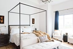 5 Tips for Creating A Master Bedroom He Will Love | white bedroom with blue accents and tan accents | four poster bed