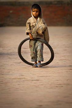 Street kid playing with a tire - Bhaktapur, Nepal - Pixdaus