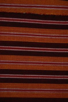 Textile: composed of six narrow strip woven cotton lengths hand sewn together selvedge to selvedge. Plain weave: dyed yellow, red, black and bleached white cotton warps and wefts. This creates yellow, white, red and dark red warp stripes which are crossed at each end by black and white weft stripes. The textile is finished by unworked warps.