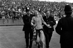 The BootBoy Look..Stripped to the waist, a man is led away by police at Brisbane Road ground before the League Division Two match between Orient and Manchester United on the opening day of the 1974/75 season. Date: 17/08/1974........17