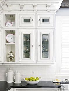 Detailed moldings and trimwork highlight the furniturelike design of these intricate cabinet doors. A mix of open shelves and white glass-front doors are finished with a gray glaze to add depth to the details and help draw attention to elegant china displayed inside.